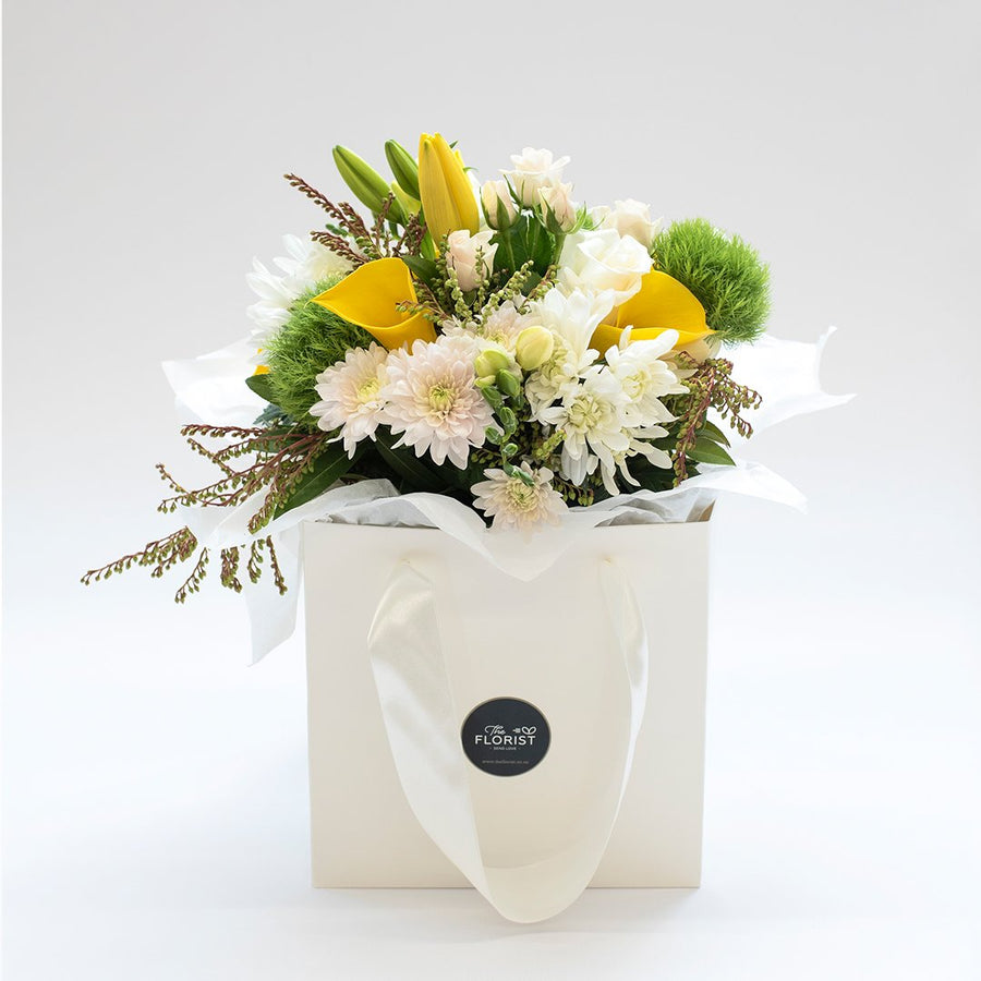 'Brilliant in Kōwhai' is a bouquet comprising of seasonal yellow and white flowers. Wrapped with a White Card wrap and satin ribbon.