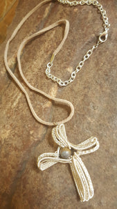 A hand woven silver cross necklace