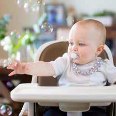 baby using pacifier clip playing with bubbles