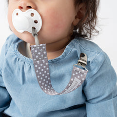 baby using BooginHead pacifier clip gray polka dots