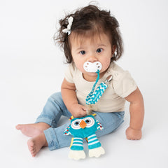 Baby using BooginHead PaciPal Owl pacifier holder