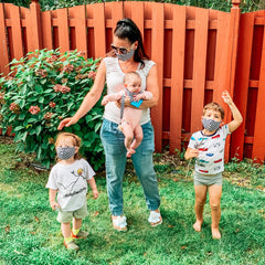 A mom with two kids and baby wearing BooginHead masks and baby products