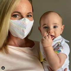 Mom wearing BooginHead face mask holding baby using BooginHead baby products