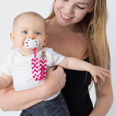Mom holding baby using BooginHead Pacifier clip