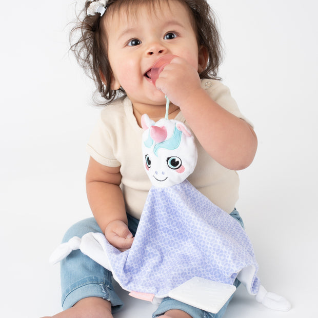 Toddler using the BooginHead Plush PaciPal Teether Blanket, Dreamer the Unicorn. Keeps track of pacifier with attaching loop. Super soft fabric from a woman owned small business. Easy to clean!