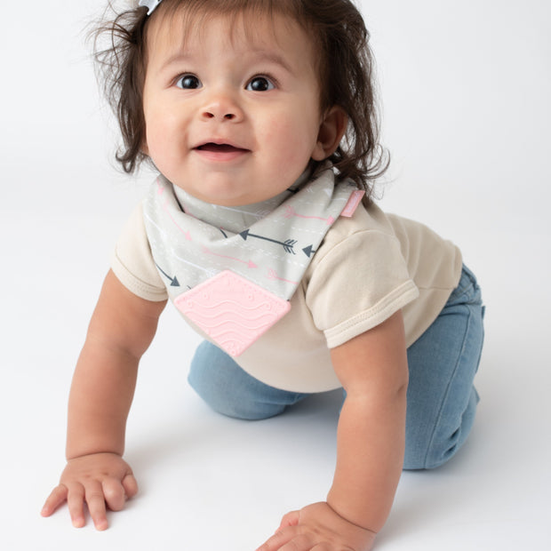 Baby girl wearing BooginHead Bandana Bib in Arrows with pink and gray designs