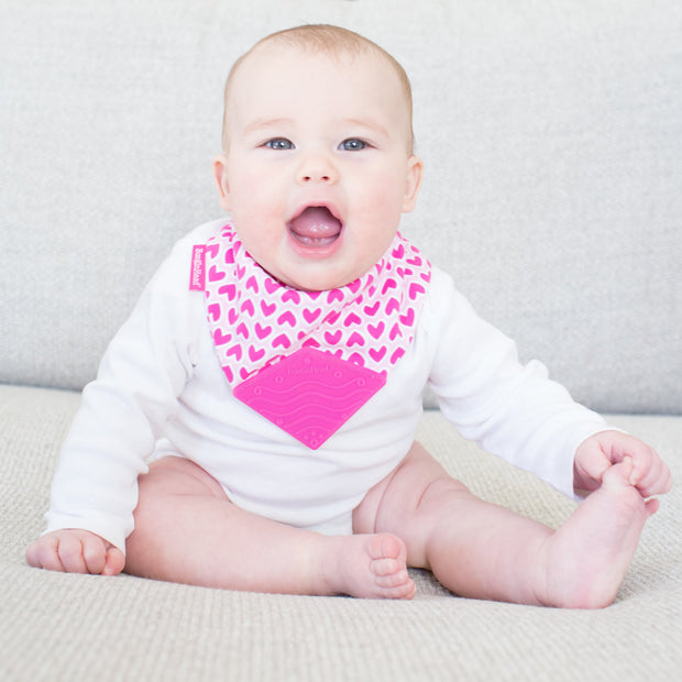 Baby girl in soft BooginHead Bandana Teether Bib in Love with pink hearts