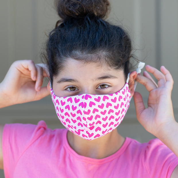 Girl wearing BooginHead Youth Face Mask in Pink Hearts