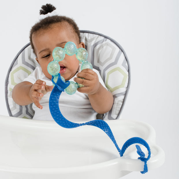 Toddler using BooginHead SippiGrip Silicone sippy cup strap in Royal Blue. Hold sippy cups, bottles and toys to high chairs and strollers