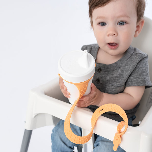 Toddler using BooginHead SippiGrip sippy cup strap in Creamsicle Orange. Hold sippy cups, bottles and toys to high chairs and strollers