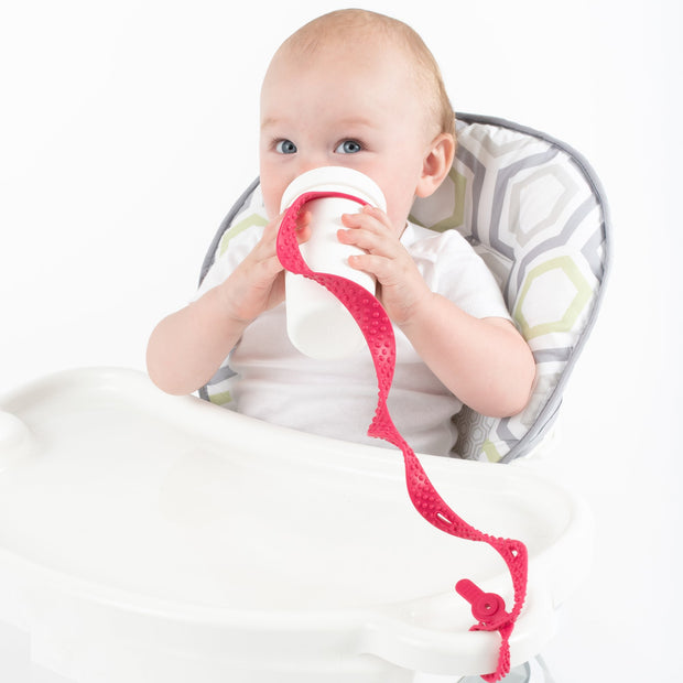 Baby using BooginHead SippiGrip Silicone sippy cup strap in Hot Pink . Hold sippy cups, bottles and toys to high chairs and strollers