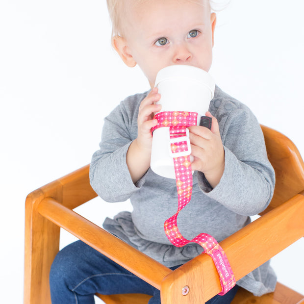 Toddler using BooginHead SippiGrip in Dottie, hot pink and white design, to keep the sippy cup clean and attached to their highchair. Adjustable strap can attach to bottles, sippy cups or toys. Essential baby and toddler supply! Easy to clean.