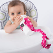 Toddler using BooginHead SippiGrip in Pink Polka Dots to keep the sippy cup clean and attached to their highchair. Size adjustable strap can attach to bottles, sippy cups or toys. Essential baby and toddler supply! Easy to clean. Bright pink and white design