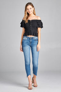 This flattering off the shoulder top has elastic smocking and lace-up detailing in the front.