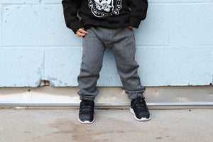 Whoever said you can't be stylish AND comfortable has never tried a pair of our City Comfort Toddler Joggers by Brooklyn + Fifth! We combined a comfortable sweatshirt fabric with cozy fleece lining and added stylish design features including a mock fly, a contrasting color back logo pocket and elastic cuffs to show off your sneakers! The result is the ultimate blend of style + comfort!  These pants have taken over the fashion industry and now you can own a pair for your stylish toddler as well!  h