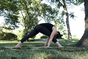 Young woman doing yoga in the park in an intense extended side angle stretch pose - Extended Side Angle Pose - Yoga - ILYNSI Yoga