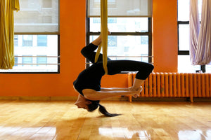 Young woman doing aerial yoga in an inverted pigeon pose - Aerial Yoga - ILYNSI Yoga