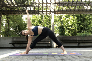 Young woman doing yoga in the park in an extended triangle stretch pose - Extended Triangle Pose - Yoga - ILYNSI Yoga
