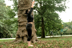 Young woman doing yoga in the park in an raised arm pose - Raised Arm Pose Pose - Yoga - ILYNSI Yoga