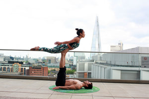 Two people practicing acro yoga on a rooftop - My first acro yoga experience - ILYNSI Yoga