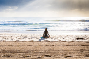 Person sitting on the beach in lotus pose meditating in the water as the waves wash over - Karma Series: The Law of Humility - ILYNSI Yoga