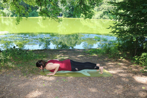 Young woman doing yoga in the park in a chaturanga dandasana or push up plank pose on an eco friendly yoga mat - Chaturanga Dandashana - Push Up Plank Pose - ILYNSI Yoga