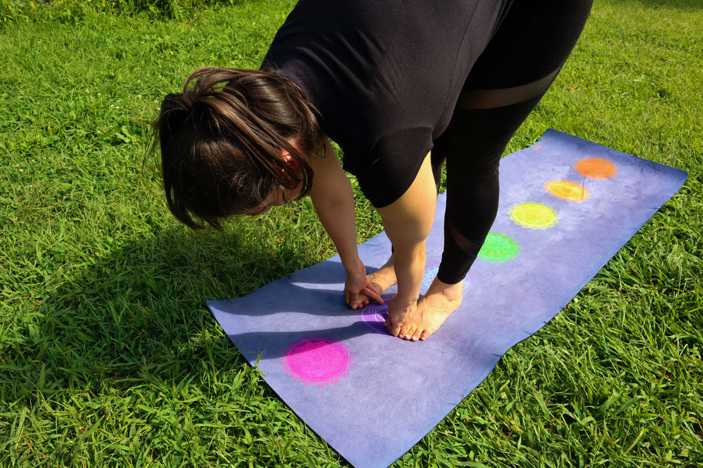 Young woman doing yoga in the park on a purple chakra yoga mat that is eco friendly. She is in big toe position. The grass is green and the sky is very blue. She is wearing yoga athleisure wear.