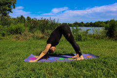 ILYNSI YOGA - Young woman doing yoga in the park in down dog position ready to jump