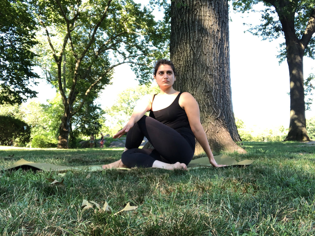 Young woman doing yoga in the park in sage pose or seated spinal twist - Sage Pose - Seated Spinal TwistPose - Yoga - ILYNSI Yoga