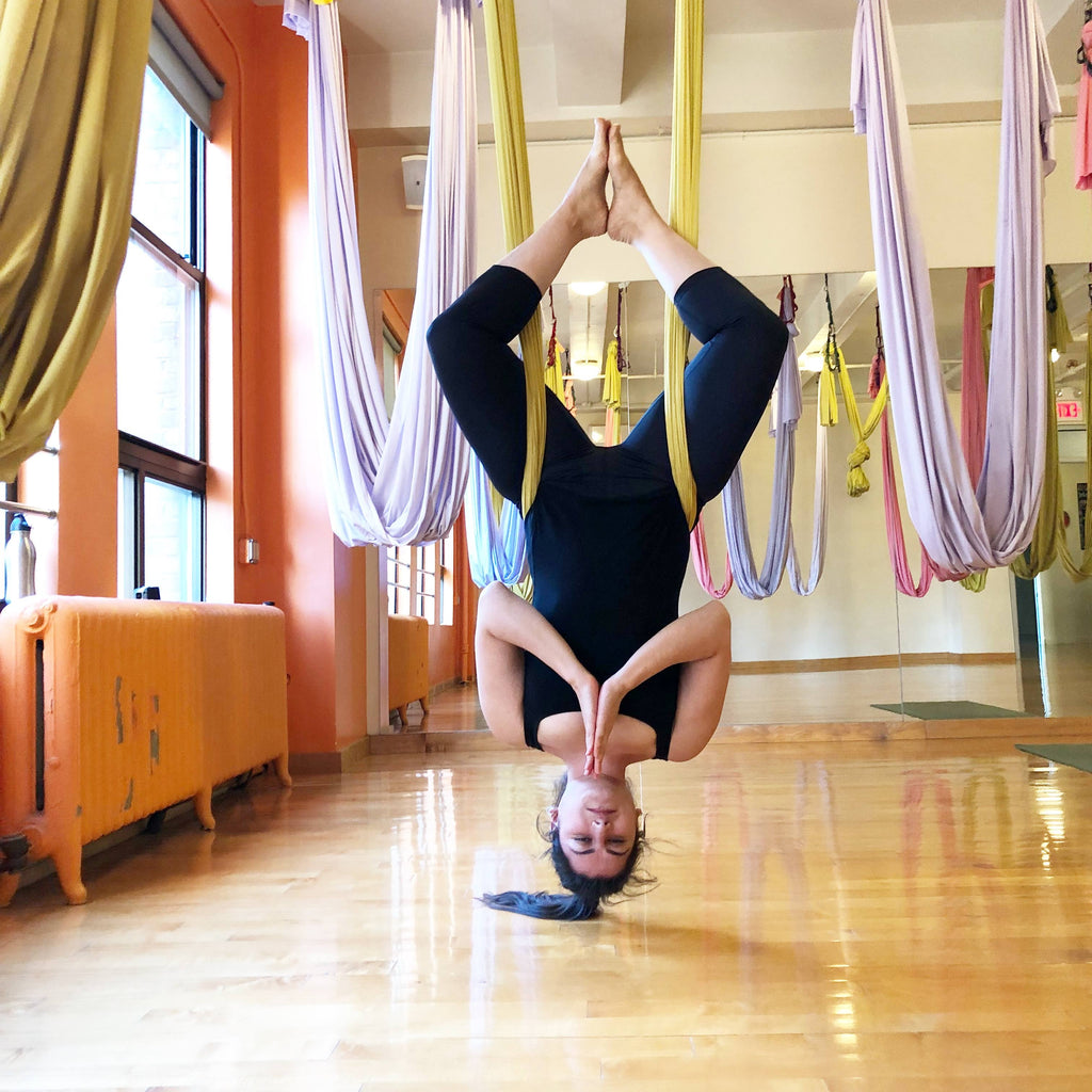 Young woman in aerial yoga class doing a headstand inversion - aerial yoga - ILYNSI Yoga
