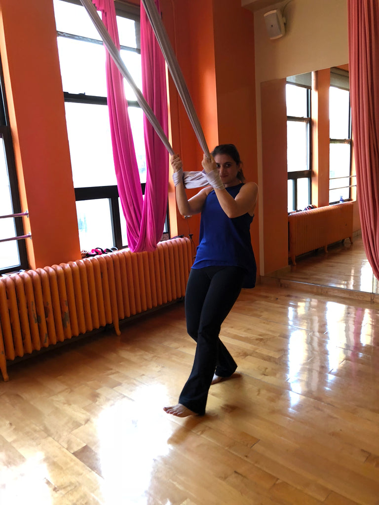 Young woman in aerial yoga class with the silks wrapped around her hands - Aerial Yoga - ILYNSI Yoga
