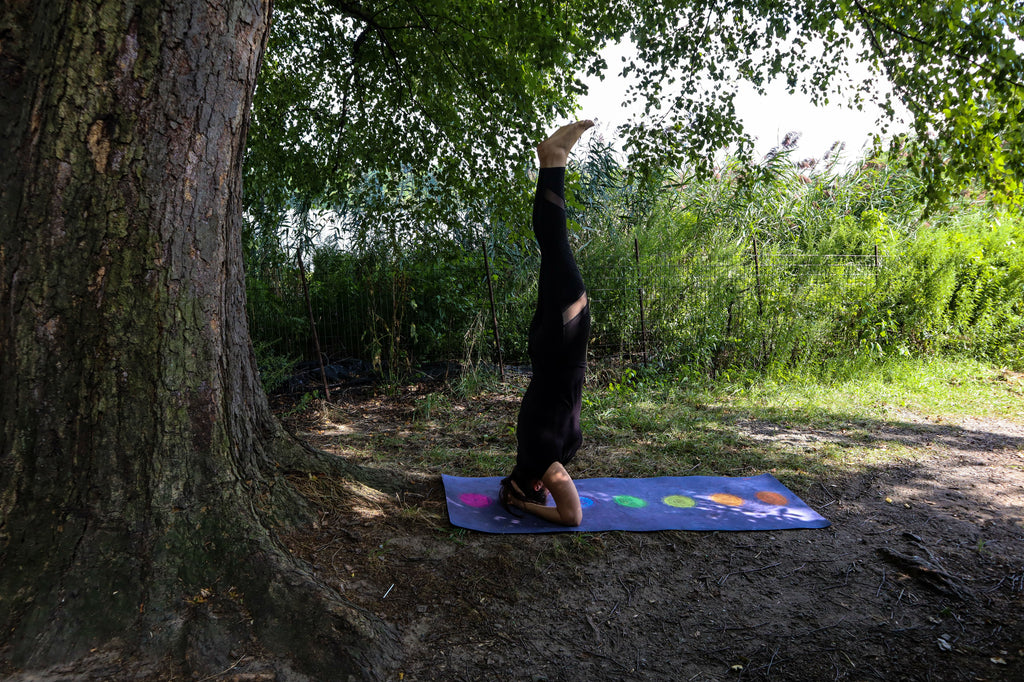 Young woman doing yoga in the park in a headstand pose beside a tree on top of a purple eco friendly yoga mat. She is wearing all black yoga attire and her hair is in a pony tail. The trees behind her are very green.