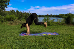 ILYNSI YOGA - Young woman doing yoga in the park jumping to the front of the mat
