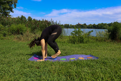 ILYNSI YOGA - Young woman doing yoga in the park in jumping to the front of the mat