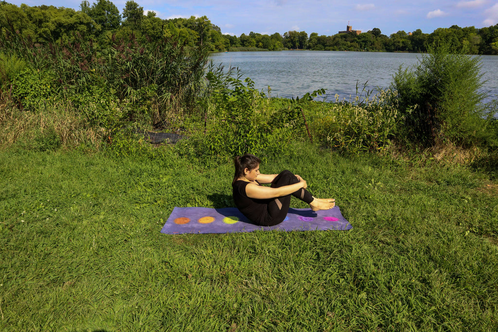 ILYNSI YOGA - Young woman doing yoga in the park in spinal roll position