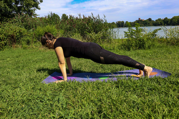 Young woman doing yoga in the park in a plank pose on an eco friendly yoga mat - Plank Pose - ILYNSI Yoga
