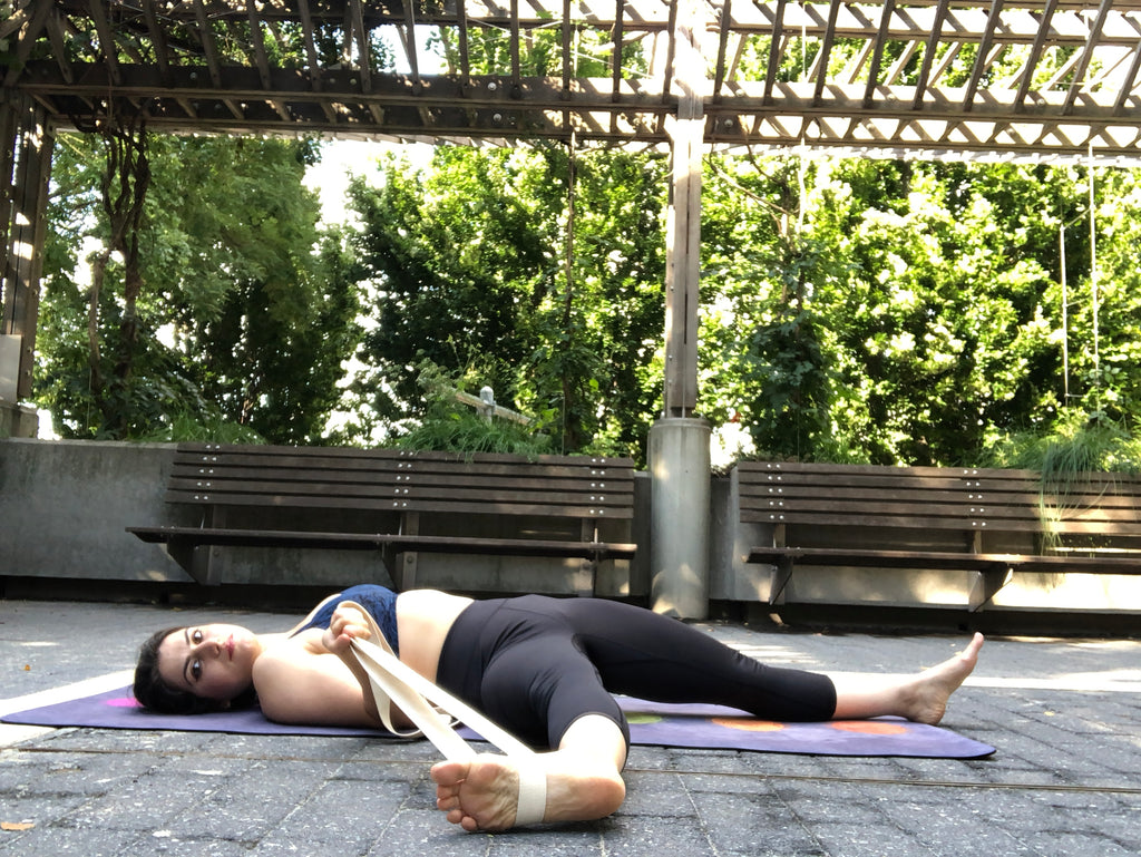 Young woman doing yoga in the park in a reclining hand to big toe pose - Reclining Hand to Big Toe Pose - Yoga - ILYNSI Yoga
