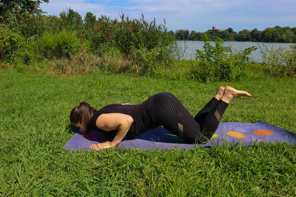 Young woman doing yoga in the park on green grass using an eco friendly yoga mat doing the knees chest chin pose or eight point salute she is wearing all black yoga athletic gear