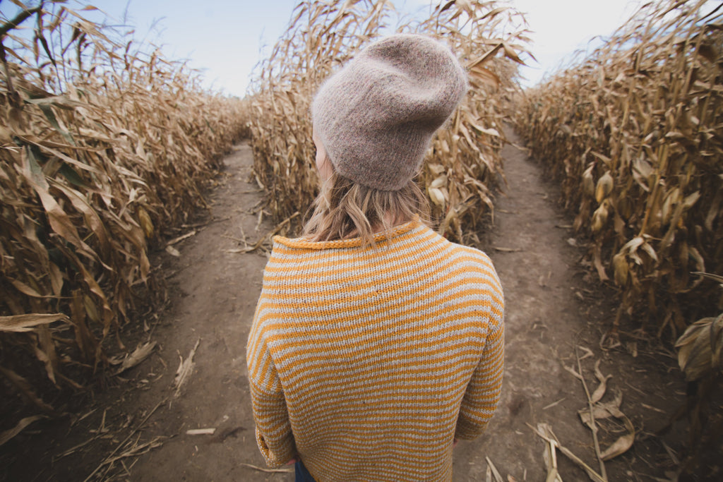 Young woman in a tan sweater standing in front aisles of wheat. She is wearing a hat - ILYNSI Yoga