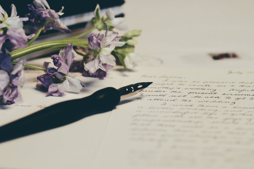 Journal with writing and with a pen and flower on top of the paper