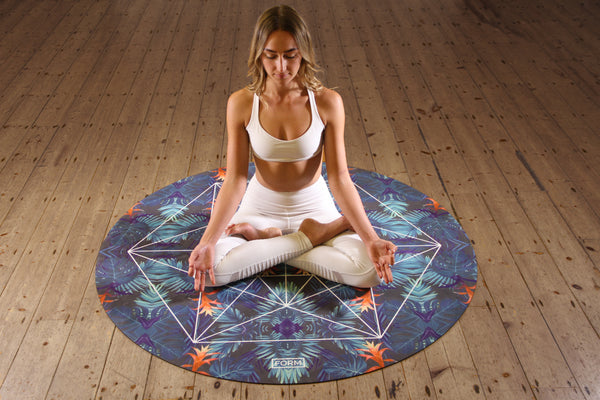 Young woman practicing yoga on a round eco friendly yoga mat indoors wearing all white yoga athleisure in a seated upright position