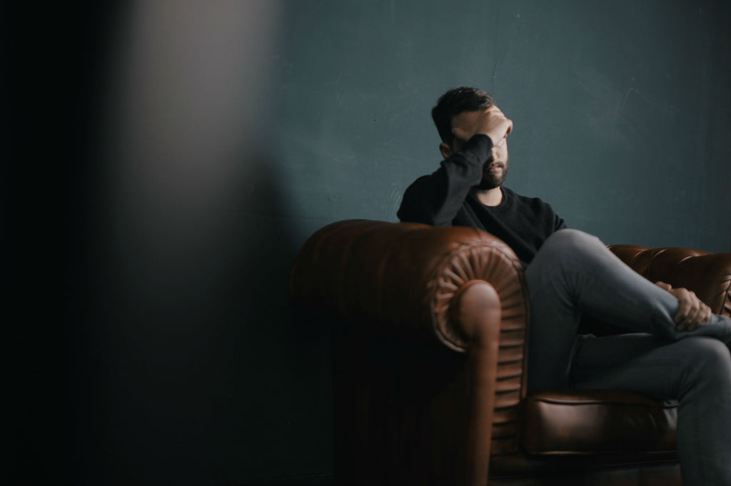 Young man sitting on a couch with his hand on his forehead in a therapy session - How to give advice - ILYNSI Yoga