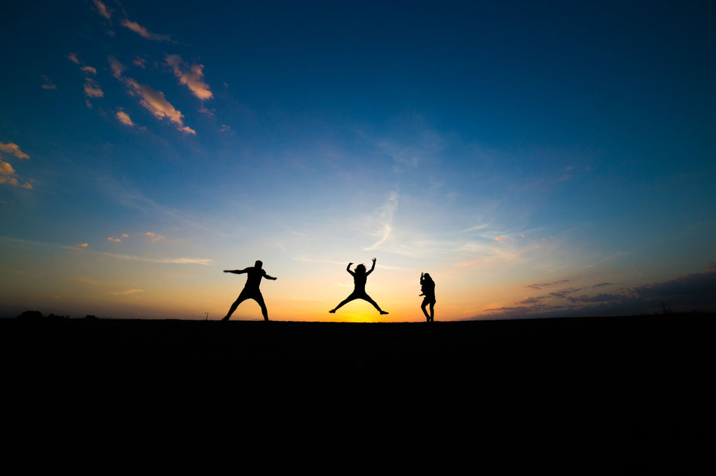 silhouette of three persons jumping in the sunset - giver yourself permission to be happy - ILYNSI Yoga