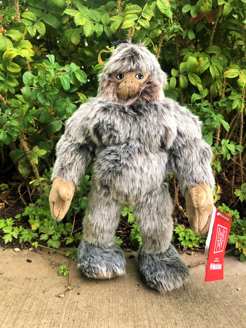 Sasquatch dog toy in front of forest background