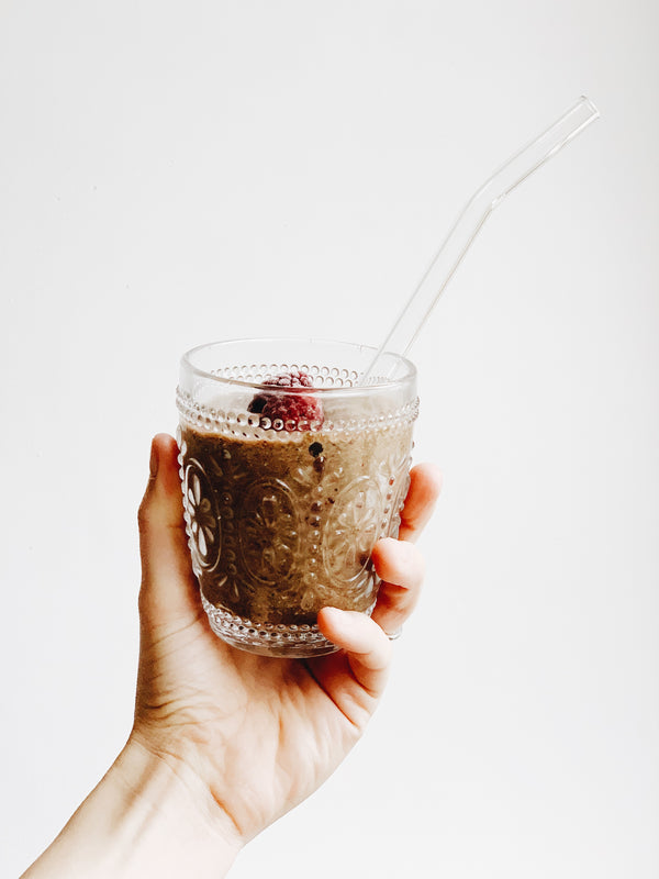 A healthy looking smoothy in a decorative glass with a glass straw topped with a raspberry