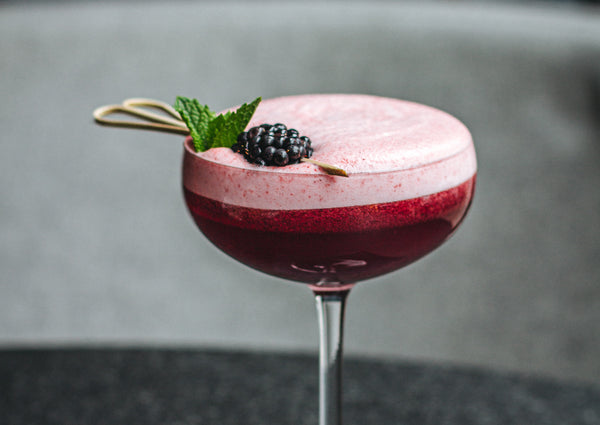 A beautiful red berry CBD cocktail in a tall glass including a cocktail stick with a blackberry and a piece of mint