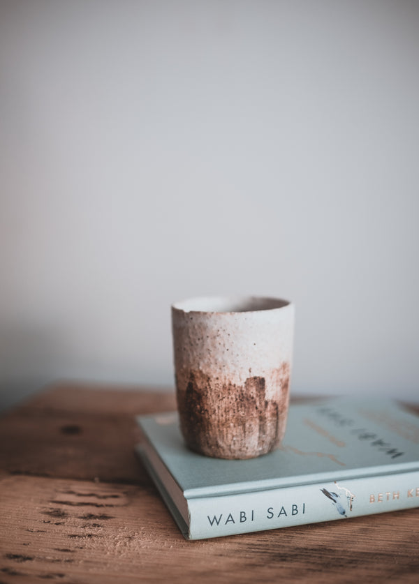 a rustic wooden table, with a turquoise book and a ceramic artisan cup