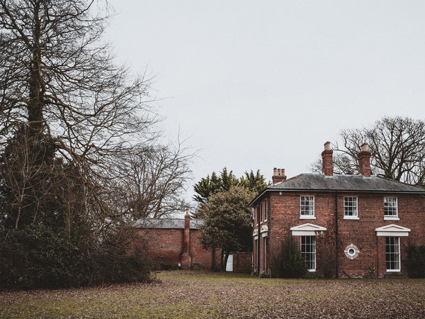 an old Georgian or Victorian red brick country house with a large tree situated in its grounds