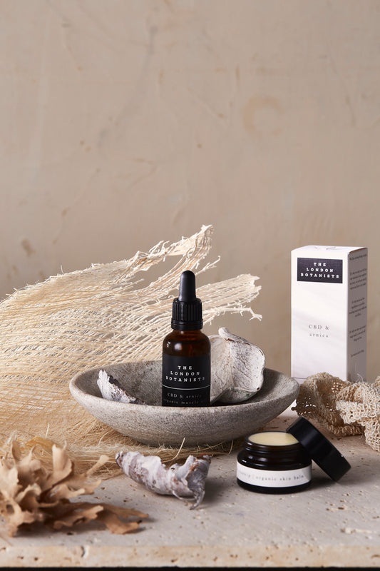 The London Botanists skin care collection laid on cement and seaside materials