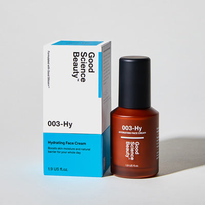 Frosted amber glass bottle and cardboard product box of 003-Hy Hydrating Face Cream against light grey background.